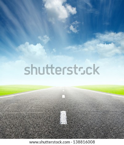 green field and road over blue cloudy sky - travel and tranportation concept