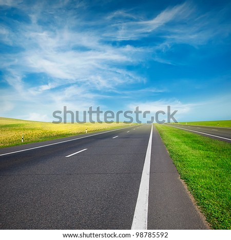 green field and road over blue sky