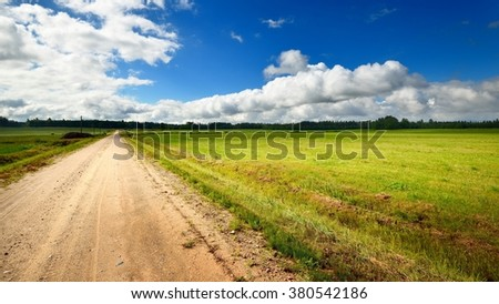 Green field and the road against stormy sky - stock photo