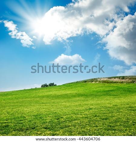 green field over sunny sky - stock photo
