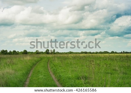 Green field, the road stretches into the distance, the trees. Blue sky with beautiful clouds. Picturesque summer landscape - stock photo
