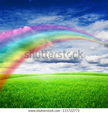 Green field under blue clouds sky with bright rainbow. Beauty nature background - stock photo