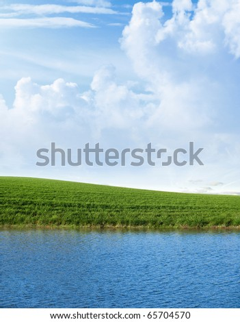 Green field with a lake in the foreground with cloudy blue sky - stock photo