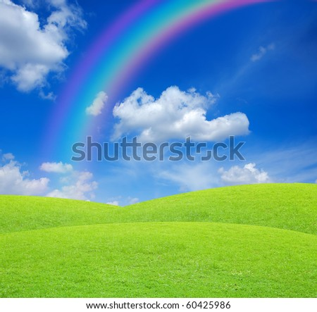 Green field with blue sky and rainbow - stock photo