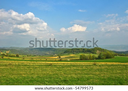 Green field with meadows and cloudscape