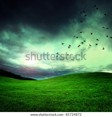 green field with storm dark clouds - stock photo