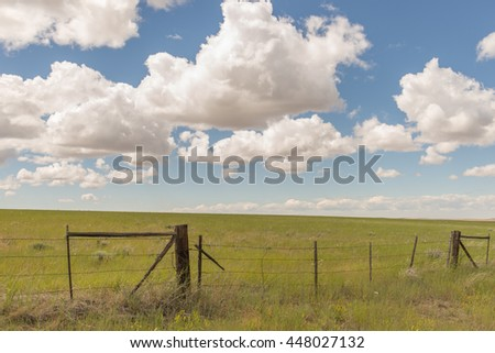 Green field with wooden gate and blue cloudy sky - stock photo
