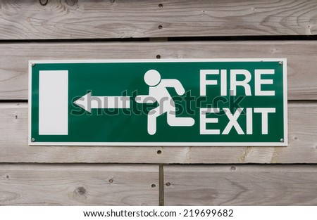 Green fire exit sign on a wood panel wall of a public building - stock photo