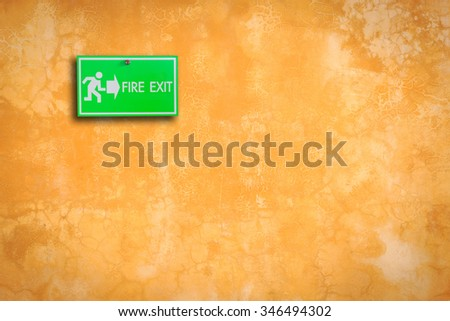 Green fire exit sign on stone wall background - stock photo