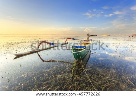 Green fishing boats populate the shoreline at the Sanur Beach, Bali, Indonesia - stock photo