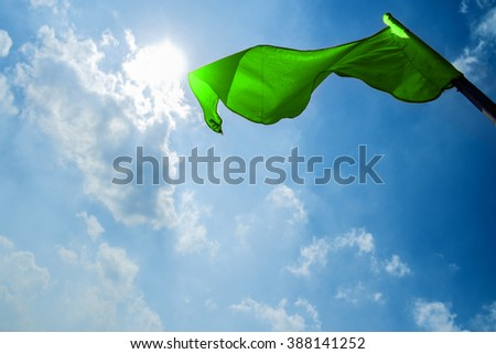 Green flag on a background of the dark blue sky with clouds. - stock photo