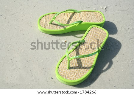 Green flip-flops on the  sand - stock photo