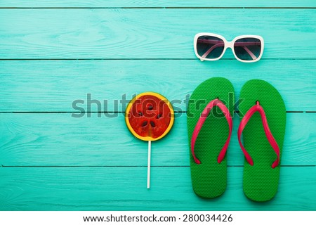 Green flip flops, sweet candy and sunglasses on blue wooden background - stock photo