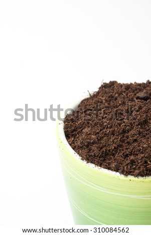 Green flowerpot filled with soil on the white background.