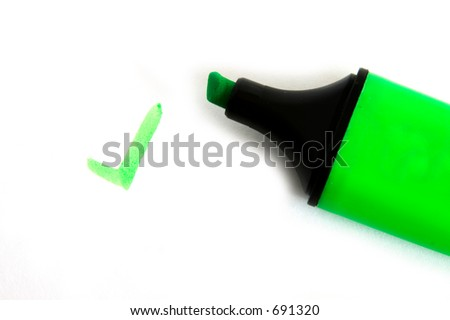 "Green fluorescent pen with a ""tick"" written on a white background"