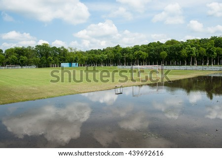green football field flooded with rain water - stock photo