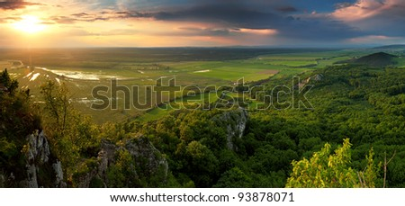 Green forest mountain at sunset with storm clouds - stock photo