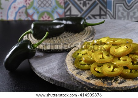 Green fresh and delicious sliced pickled jalapenos on stone with wooden background - stock photo
