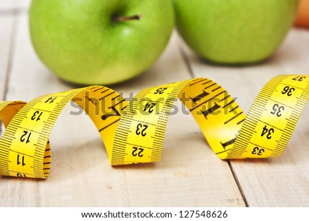 Green fresh apples with  measuring tape - stock photo