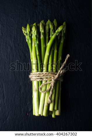Green fresh asparagus on black slate stone background. Top view - stock photo