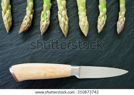 Green fresh asparagus spears with a knife on a black slate platter