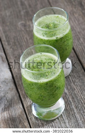 Green fruit and vegetable smoothies, top view, vertical