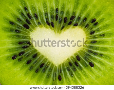 Green fruit kiwi close up with heart, green background. Kiwi fruit in the form of heart. Kiwi with seeds close-up. Heart using kiwi fruit for Valentine's day. Beautiful kiwi whole screen with heart. - stock photo