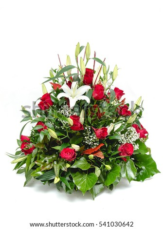 Green funeral fir wreath with red roses isolated on a white background.