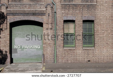 Green Garage Door In A Red Brick Wall, No Parking Day Or Night - stock photo