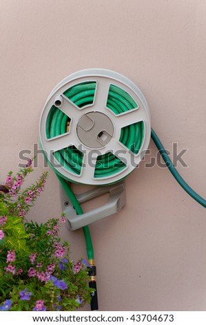 Green Garden Hose coiled on wall by plant - stock photo