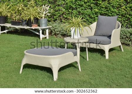green garden with an outdoor furniture lounge group with rattan chairs, sofa and table - stock photo
