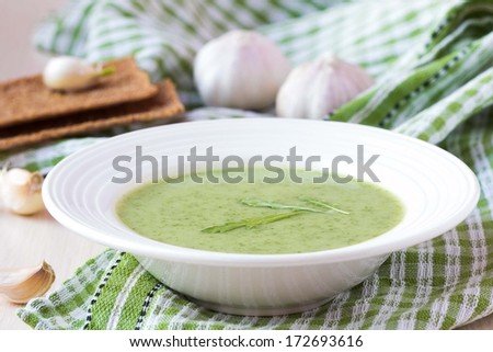 Green garlic cream soup with leaves rukola, arugula, healthy dietary vegetable dish - stock photo