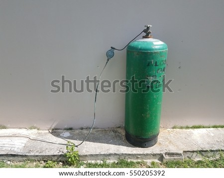 green gas tank near cement wall