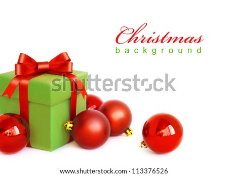 Green gift box with red ribbon bow and christmas balls around, isolated on white background