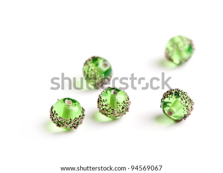 Green glass beads with golden pattern closeup on white background - stock photo