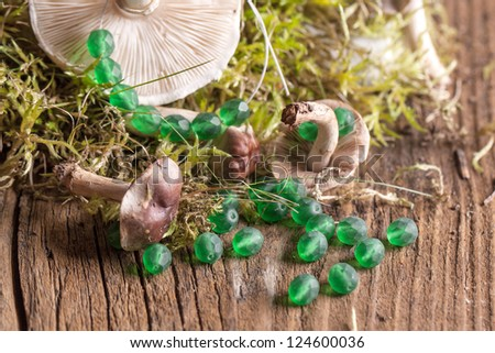 green glass beads with mushrooms and green moss on old wooden table - stock photo