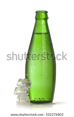 Green glass bottle of mineral water with ice on white background - stock photo