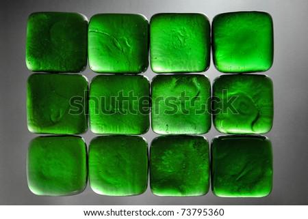 Green glass jewel blocks backlit background - stock photo
