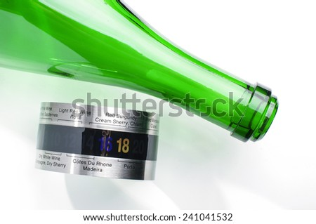 Green glass wine bottle and wine thermometer for serving - stock photo