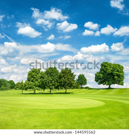 green golf course and blue cloudy sky. european field with trees landscape - stock photo
