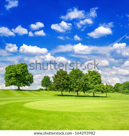 green golf course and blue cloudy sky. european field with trees landscape. sunny day - stock photo