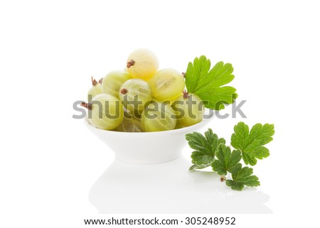 Green gooseberries in white bowl with green leaves isolated on white background. Healthy summer fruit eating.  - stock photo