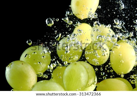 Green grape falling into water at black background - stock photo
