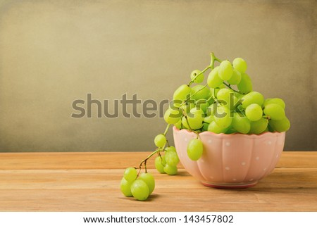 Green grapes in bowl on wooden table over grunge background