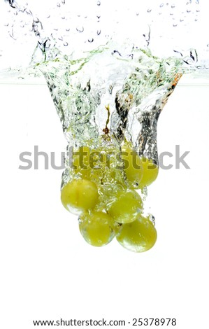 Green grapes splashing into water over a white background - stock photo