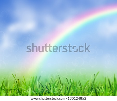 Green grass and blue sky with a rainbow. Spring nature background. - stock photo