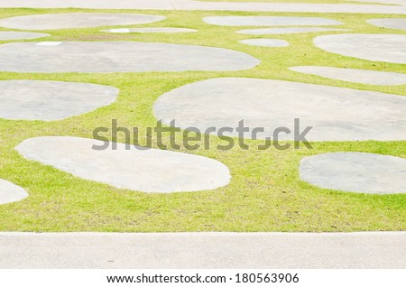 Green grass and circle concrete walkway in the park.