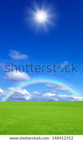 Green grass and rainbow - stock photo