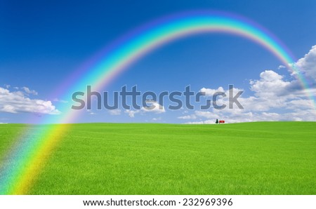 Green grass and red roof house and rainbow - stock photo