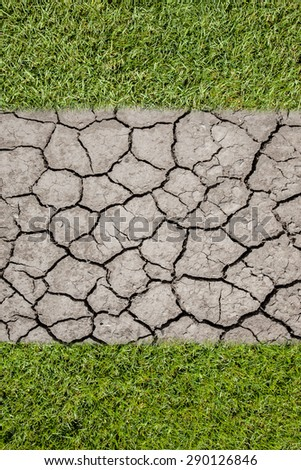 green grass and the other half is cracked dry  - stock photo